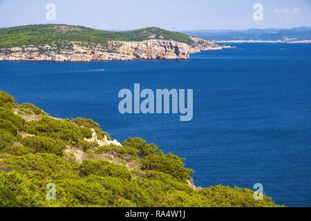 Alghero, Sardinia / Italy - 2018/08/11: Panoramic view of the Gulf of Alghero with cliffs of Punta del Giglio and city of Alghero in background - Stock Photo