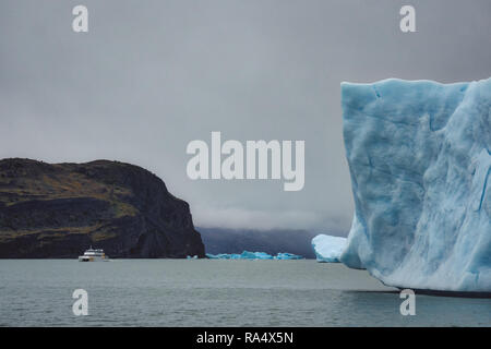 White boat on water in distance against huge rock on a cloudy day in Patagonia. Big iceberg floating in foreground - Stock Photo