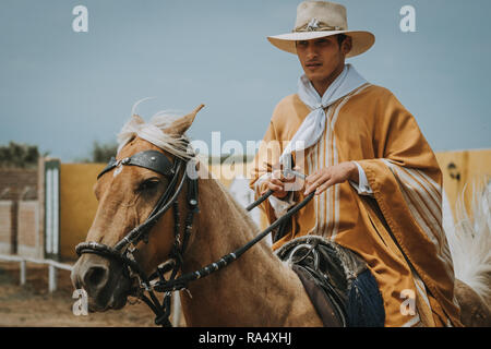 TRUJILLO, PERU - SEPTEMBER 2018 : Peruvian Morochuco cowboy on horse, in traditional clothes and hat, viewed in close-up - Stock Photo