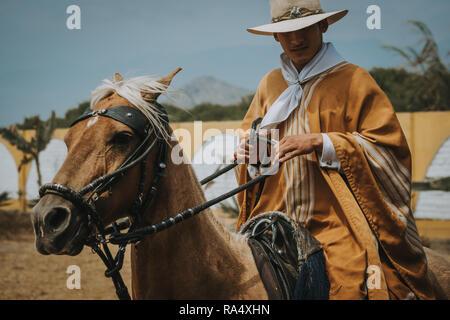 TRUJILLO, PERU - SEPTEMBER 2018 : Man in traditional clothes riding on a horse in a close up portrait, Trujillo, Peru - Stock Photo
