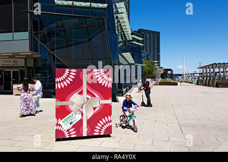 A young girl rides her tricycle around Christmas decorations in Victoria Harbour in Melbourne Docklands,Victoria Australia. - Stock Photo
