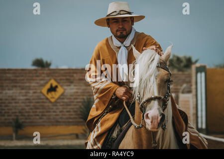 TRUJILLO, PERU - SEPTEMBER 2018 : Bearded man Peruvian cowboy riding a horse, viewed in close-up from his front with copy space - Stock Photo