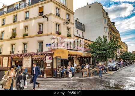 People eating lunch outside on the pavement tables at Le Vrai restaurant and cafe, Rue des Abbesses,Paris - Stock Photo