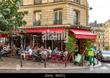 People eating lunch outside on the pavement tables at Café Bruant  restaurant and cafe,as a street sweeper goes about his work, Rue des Abbesses,Paris - Stock Photo