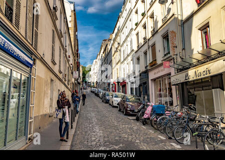 A  woman standing on a Montmartre cobbled street with parked cars ,scooters and bicycles parked outside Café Le Nazir , Rue Tholozé ,Paris - Stock Photo