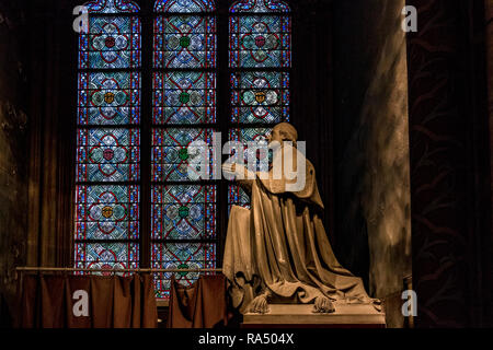 A statue of Archbishop Sibour stands in front of a stunning blue and green stained glass window at Notre-Dame Cathedral , Paris