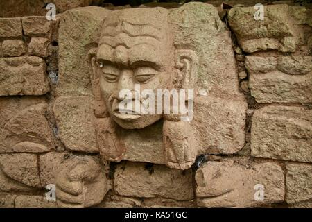 A stone carving on a Mayan warrior at jungle ruins in Honduras - Stock Photo