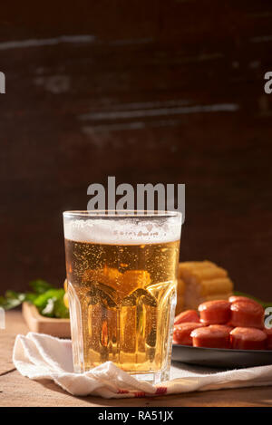 Grilled sausages with glass of beer on wooden table with copy space. - Stock Photo