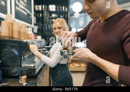 Barista man and woman making coffee, couple of young people working in coffee shop.