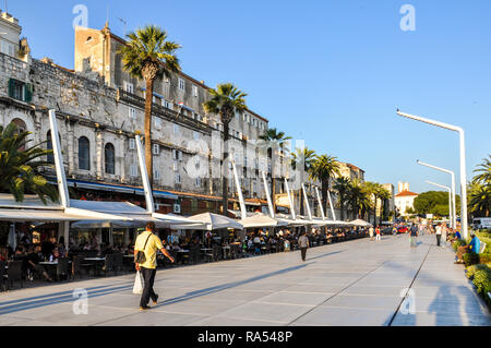 Man walking along the promenade 'Riva' in evening sunshine - Stock Photo