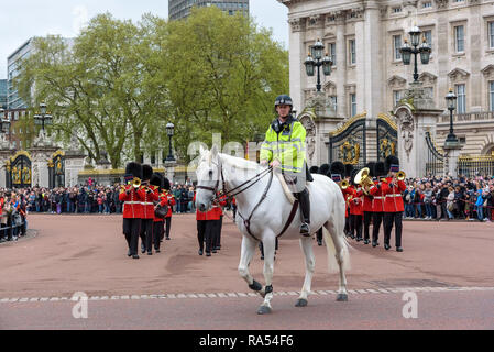 London, UK - April 29, 2018: Mounted police officer leads marching Royal Guard soldiers during changing of the guard at Buckingham Palace - Stock Photo