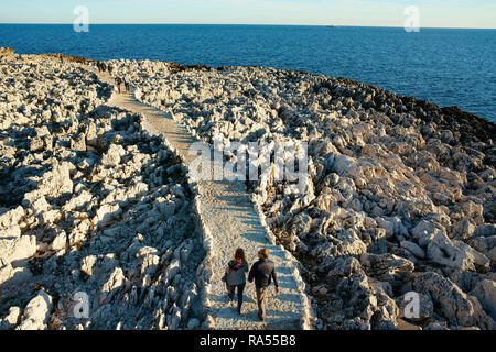 COUPLE WALKING ON A FOOTPATH IN A SEASIDE LANDSCAPE OF RAZOR-SHARP LIMESTONE RIDGES (aerial view from a 6m mast). Cap-Ferrat, French Riviera, France. - Stock Photo