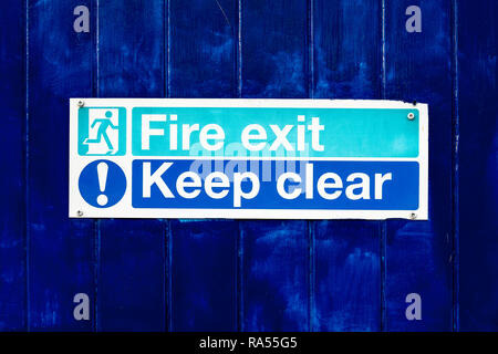 Fire exit keep clear sign on blue door - Stock Photo