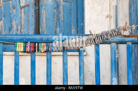 Many old clothespins are strung together on a line outside on a blue wooden balcony parapet in a Greek village - Stock Photo
