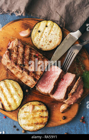 Grilled beef steak on a cutting board with vegetables, blue background. Top view, flat lay - Stock Photo
