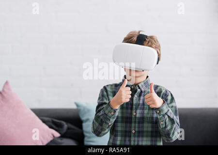 boy using virtual reality headset and showing thumbs up at home - Stock Photo