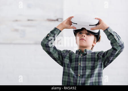 adorable boy using virtual reality headset and looking away at home - Stock Photo