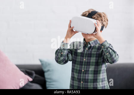 adorable little boy using virtual reality headset at home - Stock Photo