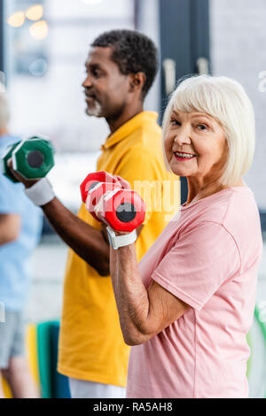 selective focus of senior woman and her african american husband doing exercise with dumbbells at gym - Stock Photo