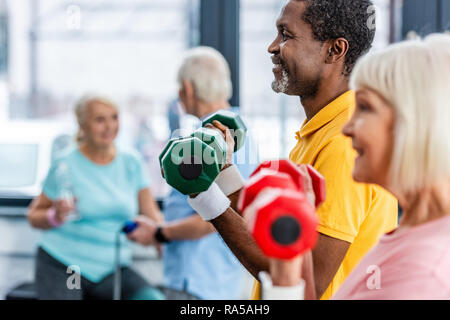 selective focus of interracial mature couple doing exercise with dumbbells at gym - Stock Photo