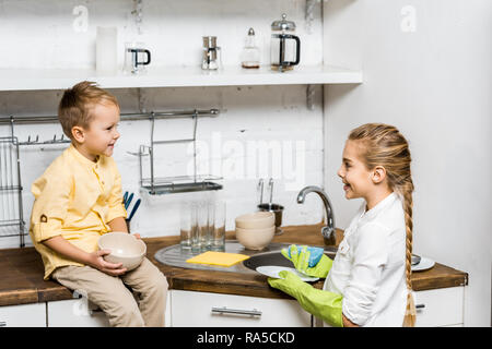 cute girl in rubber gloves washing dishes and looking at smiling boy sitting on table and holding bowl in kitchen - Stock Photo