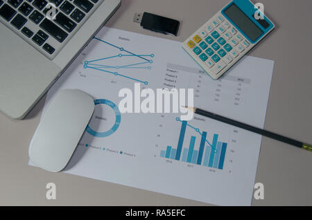 graphs and chart with computer and mouse on table. - Stock Photo