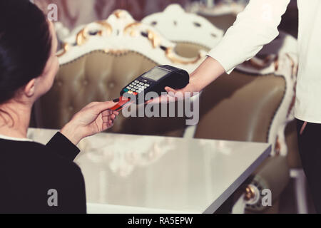 Credit card terminal for cashless payments. Cashiers hand holds credit card reader on restaurant background. Electronic finance and shopping concept. Female customer puts credit card into machine. - Stock Photo