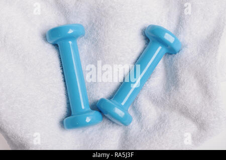 Health regime and fitness symbols. Barbells in small size, top view. Healthy lifestyle and sports concept. Dumbbells made of blue plastic on soft white cloth background - Stock Photo