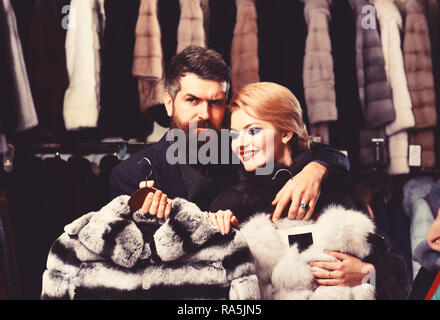 Woman with smiling face in black fur coat with bearded man. Luxury shopping concept. Couple in love holds white sable and chinchilla fur coats. Man with strict face and woman with coats in fur shop. - Stock Photo