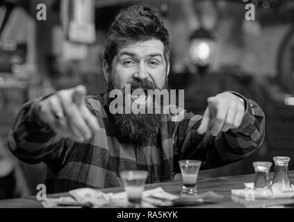 Alcohol and fun concept. Cheerful man near bar counter pointing at camera. Guy spend time in bar, defocused background. Hipster on happy face near shot cocktail. - Stock Photo