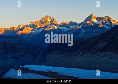 Sunrise at the summits Dent Blanche, Ober Gabelhorn and Wellenkuppe, Zermatt, Valais, Switzerland - Stock Photo