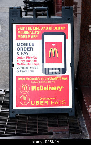 A sign outside a McDonald's in Greenwich Village promoting a new mobile app and the ability to order on McDelivery and Uber Eats. - Stock Photo