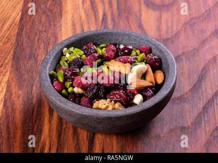 Various dried fruits and nuts in a ceramic bowl (walnut, cashew, almonds, pine nuts, hazelnuts) on a gray stone or slate background. The concept of a  - Stock Photo