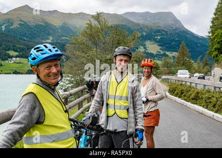 Three cyclists with mountain bikes and safety vest, on the Via Claudia Augusta cycle path, crossing the Alps - Stock Photo