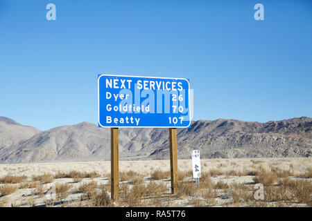 Next services blue road sign on the road from Bishop in California to Las vegas Nevada,Desert, USA - Stock Photo