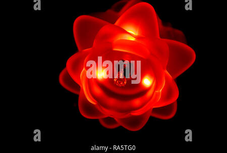 Macro closeup of a flower shaped lamp isolated in the dark, red led lights shining - Stock Photo