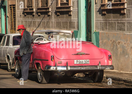 street bum in front of classic vintage American car parked on road in Havana, Cuba, Caribbean - Stock Photo