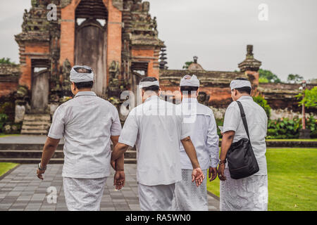 Balinese people in traditional clothes during religious ceremony at Pura Taman Ayun Temple, Bali in Indonesia - Stock Photo