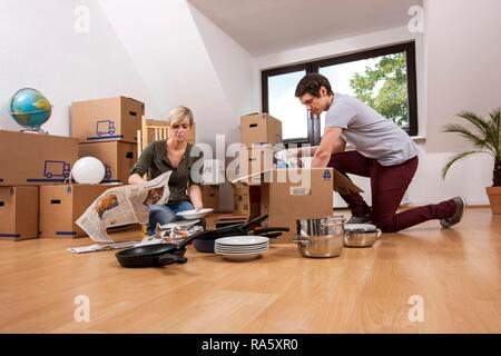 Young couple in an empty room in a new apartment unpacking the first boxes - Stock Photo