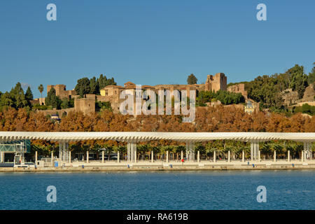 Paseo del muelle uno promenade with Alcazaba moorish castle on a hill behind, view from across the water from the harbor of Malaga, Spain - Stock Photo
