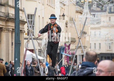 Bath, UK. 1st Jan 2019. A street entertainer plays his violin while walking on a tightrope in the centre of Bath, England on the first day of 2019 as crowds of shoppers make the most of the New Years Day sales. Credit: Phil Rees/Alamy Live News - Stock Photo