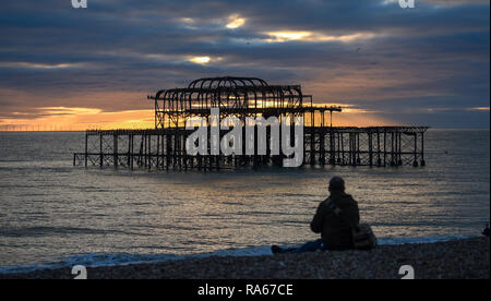 Brighton UK 1st January 2019 - A visitor watches the sun setting behind the West Pier in Brighton at the end of beautiful afternoon on the south coast of Britain Credit: Simon Dack/Alamy Live News - Stock Photo