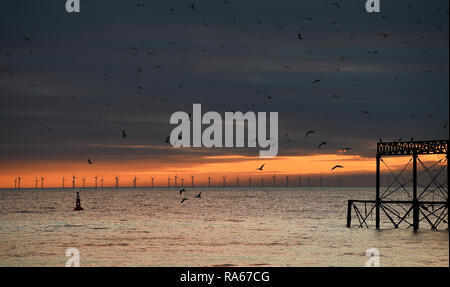 Brighton UK 1st January 2019 - The sun sets behind the West Pier with the Rampion wind farm in the distance at the end of beautiful afternoon on the south coast of Britain Credit: Simon Dack/Alamy Live News - Stock Photo