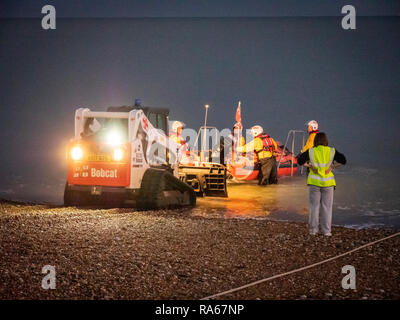Eastbourne, East Sussex, UK, 1st January 2019. The RNLI Lifeboat is launched from the beach on the south coast just as it gets dark at the South Coast seaside resort. The crew pushed the D class inshore lifeboat down the shingle beach with a small tractor and sped off into the darkness. Credit: Julian Eales/Alamy Live News - Stock Photo