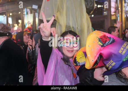 A Participant seen wearing 2019 glasses during the New Year's Eve celebrations. Despite all day rain, More than 2 million people participate at the New Year's Eve celebrations at the Times Square. - Stock Photo