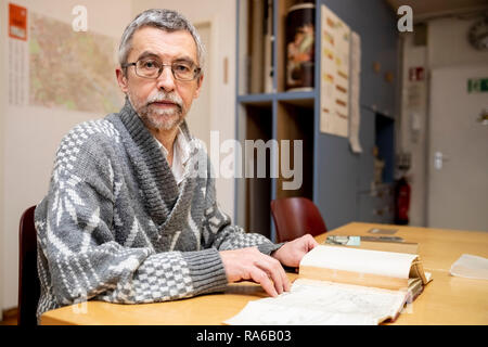 Berlin, Germany. 18th Dec, 2018. Gerhard Grosche, archive employee at the FHXB Friedrichshain-Kreuzberg Museum, sits in the archive of the FHXB Friedrichshain-Kreuzberg Museum. In Berlin, the name of a well-known place is reminiscent of a Brandenburg city, but it is written differently. (to dpa-KORR 'C or K? What the Kottbusser gate has to do with Cottbus' from 02.01.2019) Credit: Christoph Soeder/dpa/Alamy Live News - Stock Photo