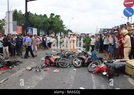 (190102) -- HANOI, Jan. 2, 2019 (Xinhua) -- Traffic police officers investigate at a road accident scene in Ben Luc district of Long An province, Vietnam, Jan. 2, 2019. A tractor trailer crashed into nearly 20 motorbikes, which stopped at a traffic light in Vietnam's southern Long An province Wednesday afternoon, killing at least six people and injuring 22 others, local media reported. The accident, involving the tractor trailer and 18 motorbikes on national road 1A, killed five people instantly and injured 23 others, of whom one died in hospital later, national radio station Voice of V - Stock Photo