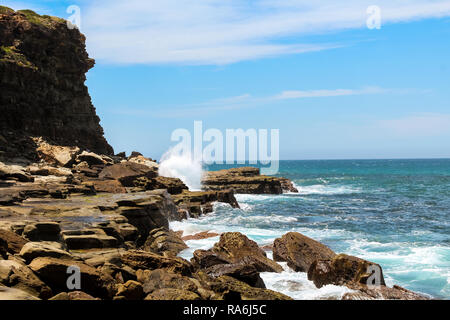Waves hitting coastal cliffs on hike to the famous Figure 8 Pools in Royal National Park near Sydney (Sydney, New South Wales, Australia) - Stock Photo