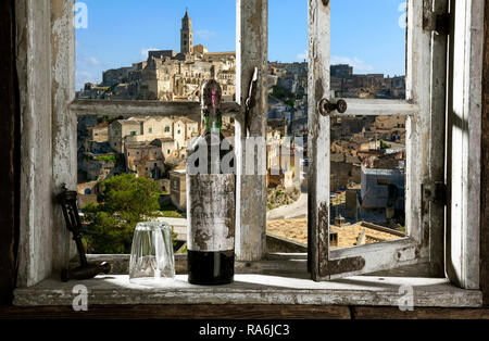 old red wine bottle in front of rustic window view on Matera, Italy - Stock Photo
