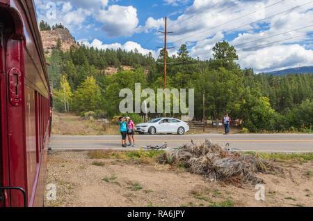 People taking Selfie photos with Durango to Silverton Narrow Gauge Railroad train at crossing - train ride from Durango to Silverton is famous. - Stock Photo